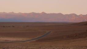 Rua solitária através do parque nacional de Vale da Morte na noite