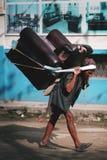 Rua velha de Carry Heavy Sofa Crossing Thamel do homem do Nepali Imagem de Stock