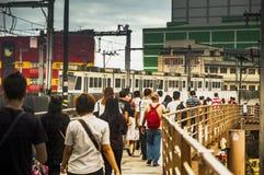 Ruas de cruzamento dos povos usando passadiço, trem, construções, baixa Fotografia de Stock