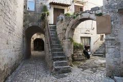 Ruas do estreito da extremidade do pavimento e pátios de Trogir, Croácia Imagens de Stock Royalty Free