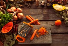 Rub carrots on a grater. Rub carrots on a grater, cooking vegetarian meal. Healthy organic food for people on a diet. Vegetables prepared for cook stock photo