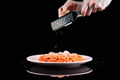 Rub grating Parmesan cheese on pasta spaghetti macaroni plate. Hands grate cheese on black background. Royalty Free Stock Photography