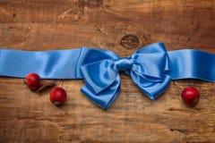 Ruban bleu de satin avec l'arc et les pommes rouges Photographie stock libre de droits