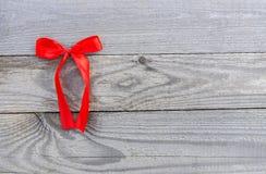 Ruban décoratif rouge avec l'arc sur le vieux fond de conseils en bois photographie stock libre de droits