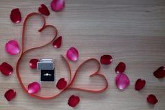 Ruban d'anneau de mariage et de coeur de deux rouges avec l'animal familier de rose de rose et de rouge Image stock