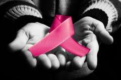 ruban de cancer à disposition sur le fond noir, la couleur dans le noir et le wh Photos stock