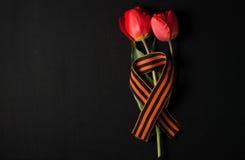 Ruban de St George et tulipes rouges sur un fond noir Image libre de droits