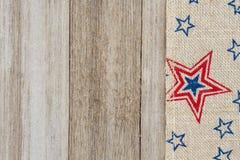 Ruban de toile de jute d'étoiles rouges et bleues des Etats-Unis sur le backgroun en bois superficiel par les agents Photos stock