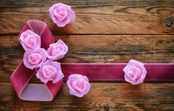 Ruban de velours, roses roses sur de vieux panneaux en bois, le 8 mars composit Image libre de droits