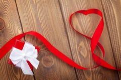 Ruban et boîte-cadeau de forme de coeur au-dessus du backgro en bois de jour de valentines Photos stock