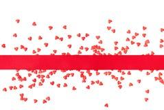 Ruban et coeurs rouges sur un fond blanc Photo stock