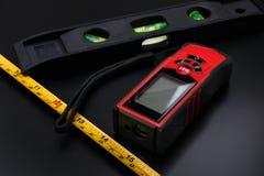 Ruban métrique, bande de laser et construction de niveau sur la surface mate noire image libre de droits