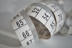 Ruban métrique blanc de longueur de mesure de bande en mètres et centimètres sur la surface d'isolement comme symbole d'outil emp photographie stock
