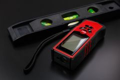 Ruban métrique de laser et construction de niveau sur la surface mate noire images stock
