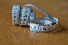 Ruban métrique de longueur de mesure dans les centimètres et des mètres, fréquemment utilisés pour mesurer le périmètre du corps  Image libre de droits