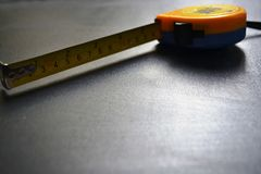 Ruban métrique de mesure sur le fond noir image libre de droits