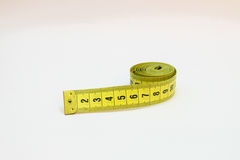 Ruban métrique jaune dans des mètres et pouces dans une spirale Images stock