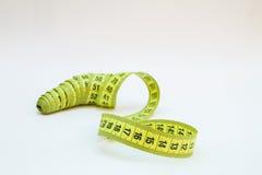 Ruban métrique jaune dans des mètres et pouces dans une spirale Photos stock