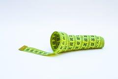 Ruban métrique jaune dans des mètres et pouces dans une spirale Photo stock