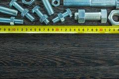 Ruban métrique nuts de joint de boulon sur le conseil en bois Image libre de droits