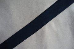 Ruban noir diagonal cousu au tissu gris-clair photographie stock
