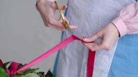 Ruban professionnel de coupe de fleuriste de bouquet de mariage à l'atelier, fleuriste Fermez-vous vers le haut du tir banque de vidéos