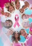 Ruban rose avec des femmes de conscience de cancer du sein remontant des mains Photos stock