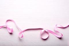 Ruban rose sur la table en bois légère Photographie stock libre de droits