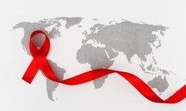 Ruban rouge de coeur de conscience de SIDA sur la carte du monde Photographie stock