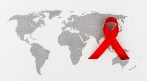 Ruban rouge de coeur de conscience de SIDA sur la carte du monde Photo libre de droits
