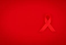 Ruban rouge de coeur de conscience de SIDA sur le fond rouge Photographie stock