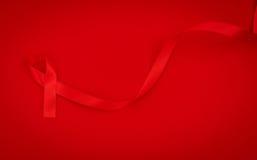 Ruban rouge de coeur de conscience de SIDA sur le fond rouge Photos stock