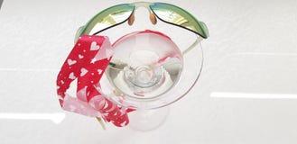 Ruban rouge de coeurs et lunettes de soleil vertes de miroir sur le verre de vigne images stock