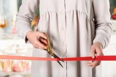 Ruban rouge de coupe de femme avec des ciseaux à l'événement cérémonieux photo libre de droits