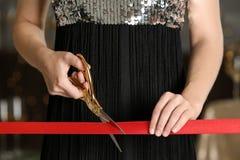 Ruban rouge de coupe de femme avec des ciseaux à l'événement cérémonieux images libres de droits