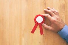 ruban rouge de récompense au-dessus de table en bois images stock