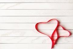 Ruban rouge de satin dans la forme de deux coeurs sur le fond en bois image stock