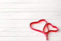 Ruban rouge de satin dans la forme de deux coeurs sur le fond en bois photos stock