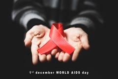 Ruban rouge sur les paumes et le texte Journée mondiale contre le SIDA du 1er décembre Photos libres de droits