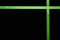 Ruban vert de satin sur un fond coloré images libres de droits
