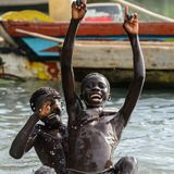 Unidentified local boys swim in water during a high tide. RUBANE, GUINEA BISSAU - MAY 4, 2017: Unidentified local boys swim in water during a high tide royalty free stock photo