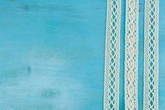 Rubans blancs de dentelle sur le fond en bois bleu Image libre de droits