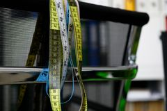 Rubans de mesure accrochant sur une chaise noire image stock