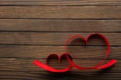 Rubans en forme de coeur sur la table Images stock