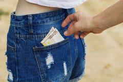 Rubare valuta dalla tasca dei jeans in assenza dei mindfulnes immagine stock
