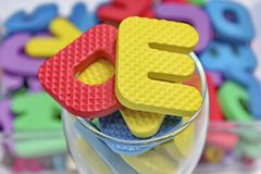 Rubber alphabets and glass Stock Photos