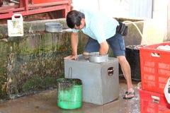 Rubber arbetare som gör ren den rubber behållaren Royaltyfri Fotografi