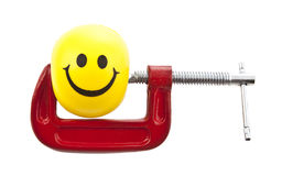 Rubber ball with a smiley face printed. On it compresses vise Royalty Free Stock Image
