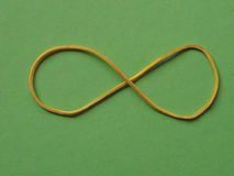 Rubber band infinity sign. Rubber band as an infinity symbol over green background royalty free stock photo