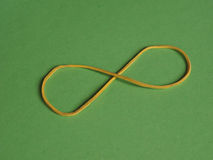 Rubber band infinity sign. Rubber band as an infinity symbol over green background royalty free stock photography